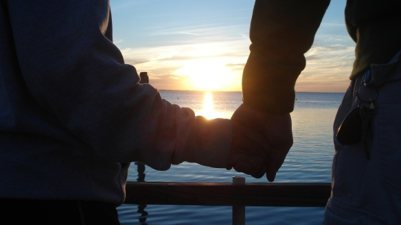 sunset holding hands